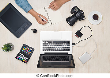 Male photographer designer working with tablet at desk.