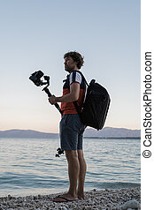 Male photographer holding his camera on gimbal stick