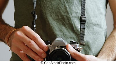 Male photographer standing with digital camera in photo...
