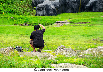 Male Photographer taking a Landscape picture of mountain.