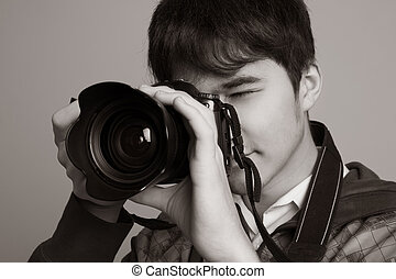 Male photographer taking photos with DSLR digital camera.