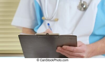 Male physician doctor writing rx prescription on clipboard for his patients