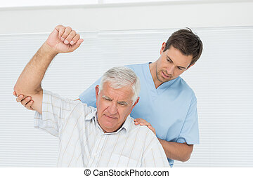 Male physiotherapist assisting senior man to raise hand in...