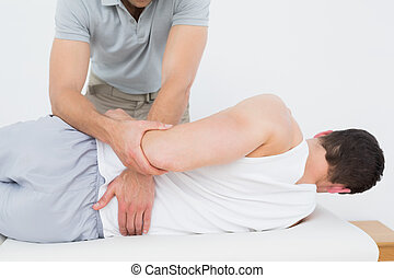 Male physiotherapist examining mans back in the medical ...