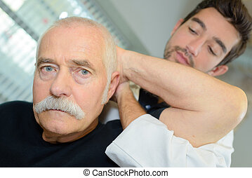 male physiotherapist examining the neck of an elderly man