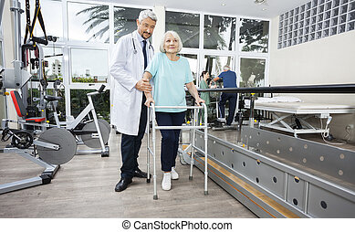 Male Physiotherapist Helping Female Patient With Walker