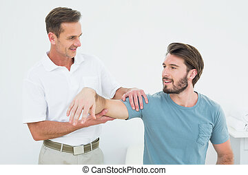 Male physiotherapist massaging a man's arm