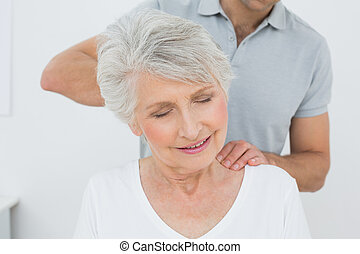 Male physiotherapist massaging a senior woman's neck in the...