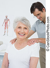 Male physiotherapist massaging a senior woman's shoulders in...