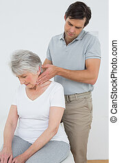 Male physiotherapist massaging a senior woman's neck