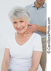 Male physiotherapist massaging a senior woman's neck