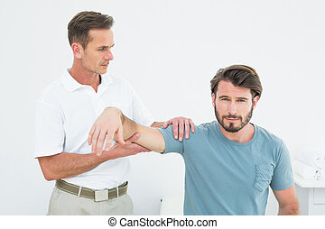Male physiotherapist massaging a young man's arm