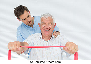 Male physiotherapist massaging senior mans back