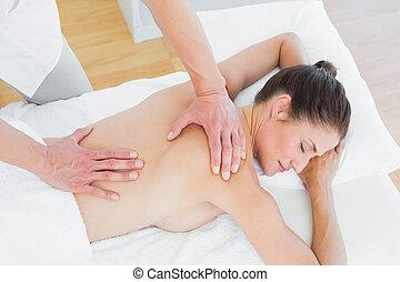 Male physiotherapist massaging woman's back