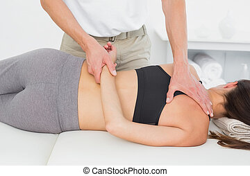 Male physiotherapist massaging woman's body in the medical...