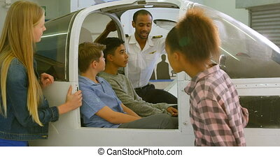 Male pilot explaining about aeroplane to kids 4k - Male...
