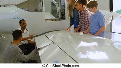 Male pilot explaining about aeroplane to kids 4k - Male...