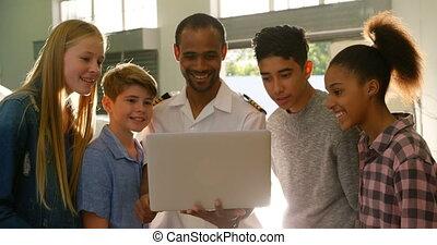 Male pilot training kids on laptop 4k - Male pilot training...