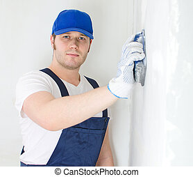 Male plasterer in baseball cap polishing the wall.