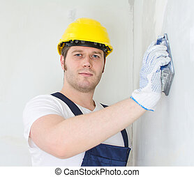 Male plasterer in hard hat polishing the wall.