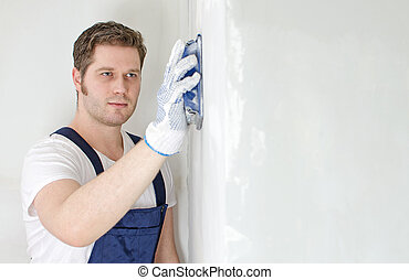 Male plasterer polishing the wall. Space for text.