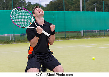 Male player fell on his knees and made a fist because of the win in tennis match