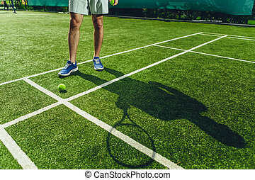 Male playing tennis on field