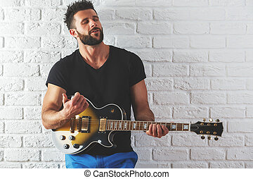 Male playing the guitar - Portrait of attractive caucasian...