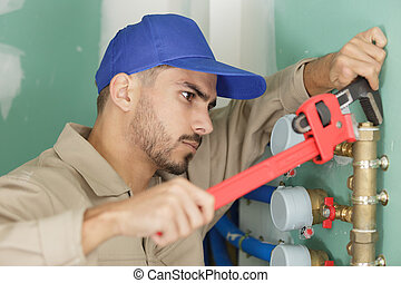 male plumber fixing water meter with adjustable wrench