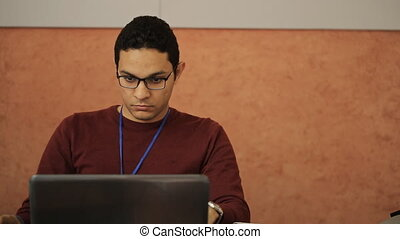 Male post-graduate with glasses and a red sweater sitting working at a laptop, looking for information for research.