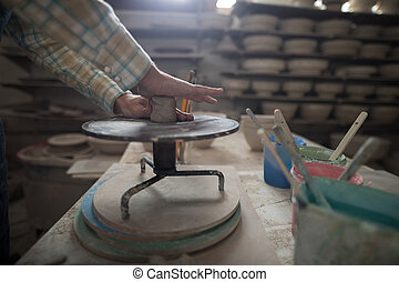 Male potter molding a clay on pottery wheel