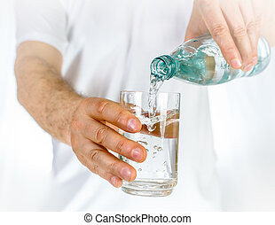 Male pouring water from bottle to glass