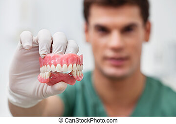 Male practitioner holding dental mold - Close-up of male...