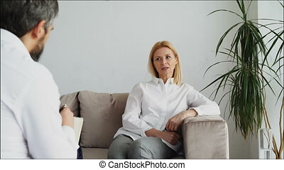 Male psychoanalyst listening adult female patient and writing notes in psychologist office