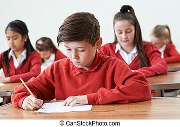 Male Pupil At Desk Taking School Exam