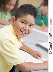 Male pupil in elementary school classroom writing at desk