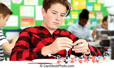 Male Pupil Using Molecular Model Kit In Science Lesson - Boy...