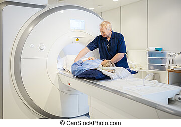 Male Radiologist Preparing Young Woman For MRI Scan - Male...