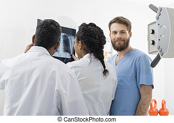 Male Radiologist With Colleagues Examining X-ray In Hospital