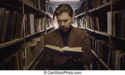 Male reading book in library