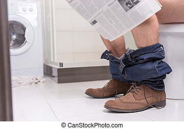 Male reading newspaper while sitting on the toilet seat