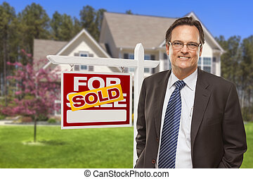Male Real Estate Agent in Front of Sold Sign and House -...