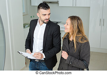 male real estate agent with clipboard indoors