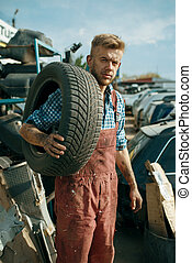 Male repairman holds tire on car junkyard