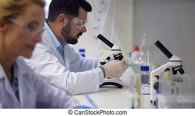 Male researcher looking through microscope in lab -...