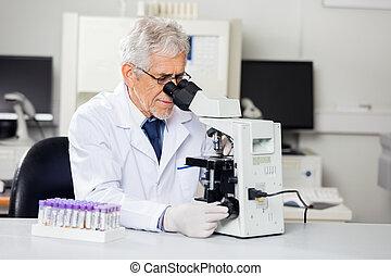 Male Researcher Using Microscope In Lab - Senior male...