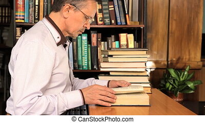 Male  researching with a book in a library