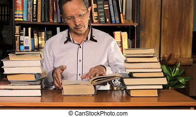 Male researching with a book in a library, outlines, reads a...
