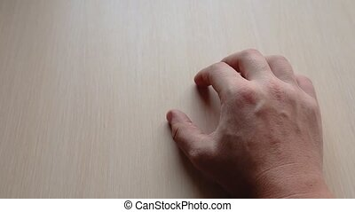 male hand on the table - male right hand is tapping his...