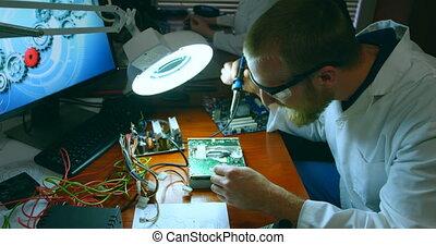 Male robotic engineer assembling circuit board at desk 4k